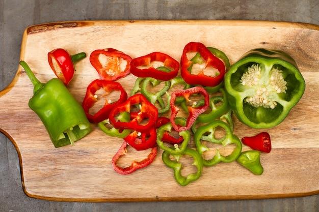 Ломтики красного и зеленого перца на деревянной кухонной доске в виде сверху