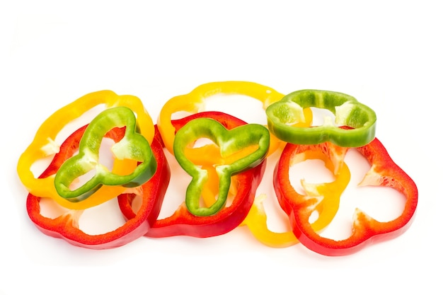 Ломтики красного, зеленого и желтого перца на белом фоне в виде сверху