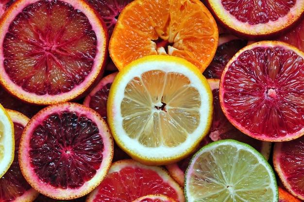 赤いシチリアオレンジタンジェリンレモンとライムの背景のスライス