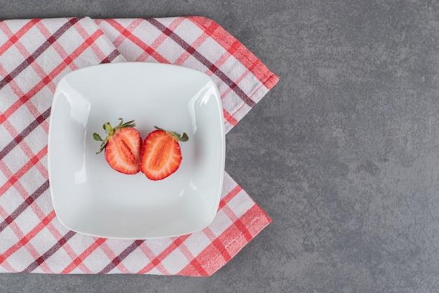 Кусочки красной клубники на белой тарелке. фото высокого качества