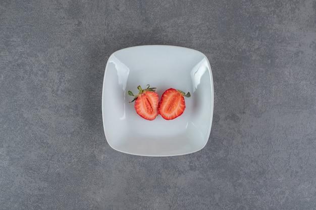 하얀 접시에 빨간 딸기 조각입니다. 고품질 사진
