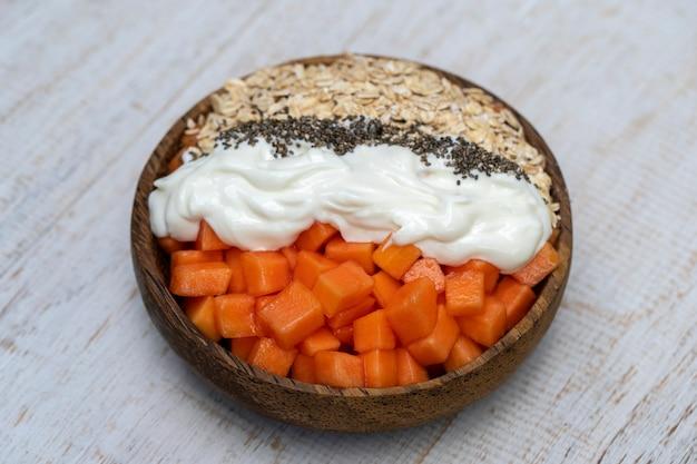 Ломтики спелых сладких плодов папайи с овсяными хлопьями, семенами чиа и белым йогуртом на кокосовой миске