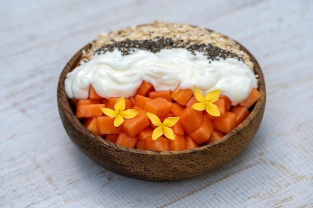 Дольки спелых сладких плодов папайи с овсяными хлопьями, семенами чиа и белым йогуртом