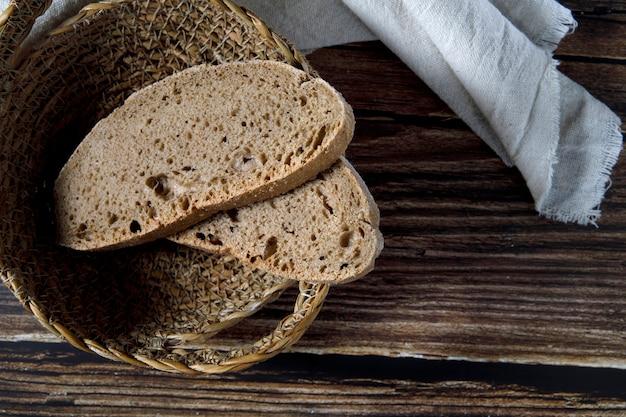 Ломтики деревенского хлеба в плетеной миске на деревянном столе