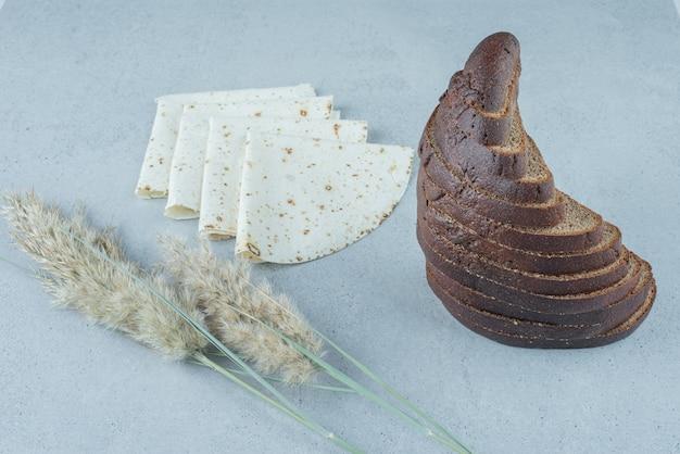 Ломтики ржаного хлеба и лаваша на каменной поверхности с пшеницей