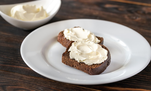 Ломтики ржаного хлеба со сливочным сыром на белой тарелке