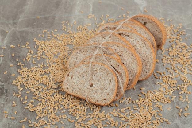 Ломтики ржаного хлеба с зернами на мраморной поверхности. фото высокого качества