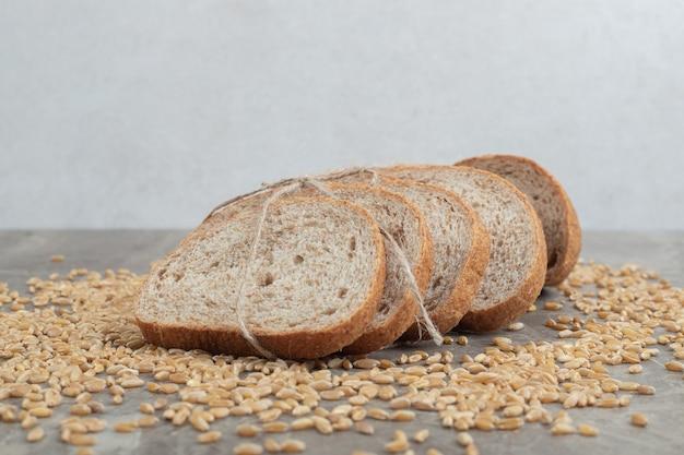Кусочки ржаного хлеба с зернами на мраморном столе. фото высокого качества