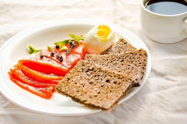 塩漬けの生の魚の切り身のスライスと卵とそば粉のグルテンフリーのパン。古ダイエットミール。健康的な高タンパク質および低炭水化物製品のコンセプト。