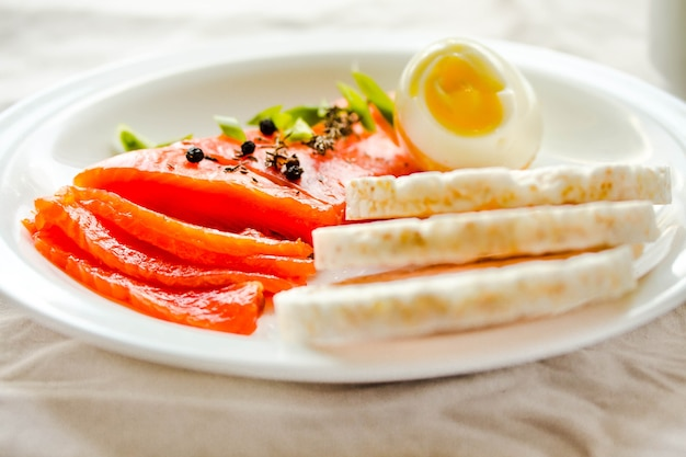 塩漬けの生の魚の切り身と卵とお餅のスライス。良い脂肪源の選択-健康的な食事の概念。ケトジェニックダイエットのコンセプト。セレクティブフォーカス