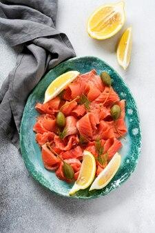 회색 콘크리트 배경의 세라믹 접시에 케이퍼, 레몬, 딜을 넣은 소금에 절인 연어 조각. 평면도