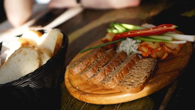 燻製ブリスケット、脂肪ベーコン、乾燥唐辛子、暗い木製のテーブルの上のパンのスライス。上面図