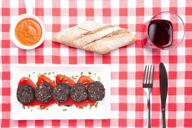 Ломтики испанского черного пудинга на перцах пикильо в белой тарелке на красной клетчатой скатерти