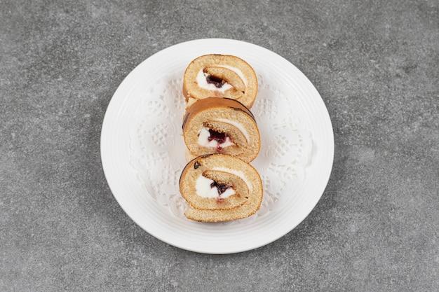 白いプレート上の甘いロールケーキのスライス