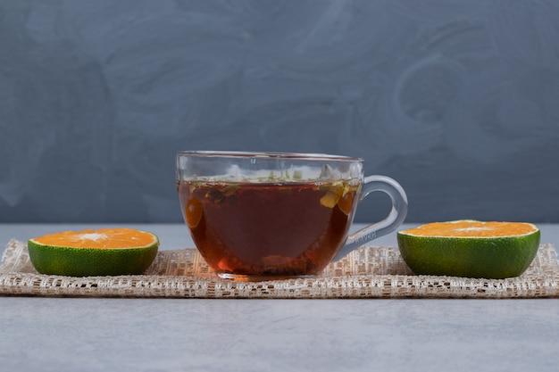 Кусочки мандаринов и чашка черного чая на мраморном столе. фото высокого качества