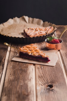 Slices of tasty pie on baking dish and paper