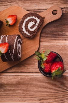 Slices of tasty roll and strawberries on wooden table