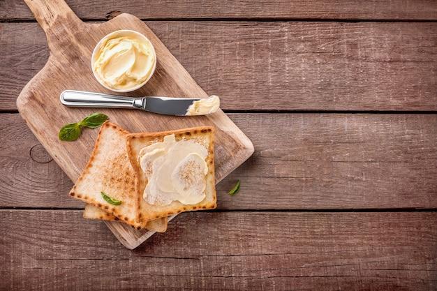 木製のまな板にバターとトーストパンのスライス