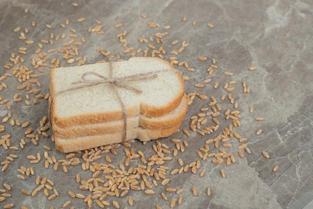 대리석에 곡물과 토스트 빵 조각. 고품질 사진