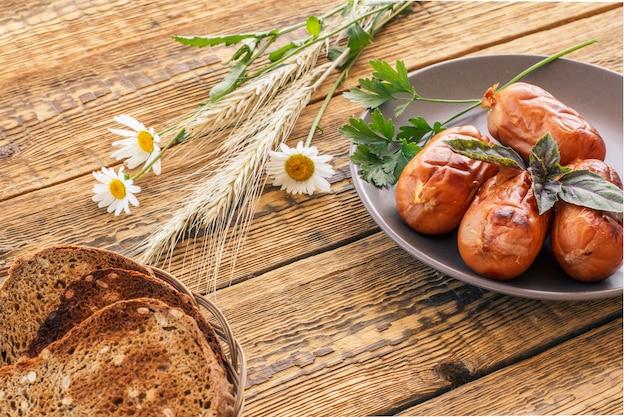 籐のバスケットにトーストをスライスし、皿にバジルとパセリを添えたソーセージのグリル。背景に木の板がある上面図。