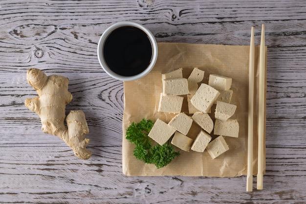 Ломтики сыра тофу, соевый соус, корень имбиря и деревянные палочки. соевый сыр. вегетарианский продукт. плоская планировка.