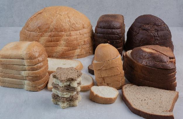白い背景の上の焼きたてのパンの様々なスライス。