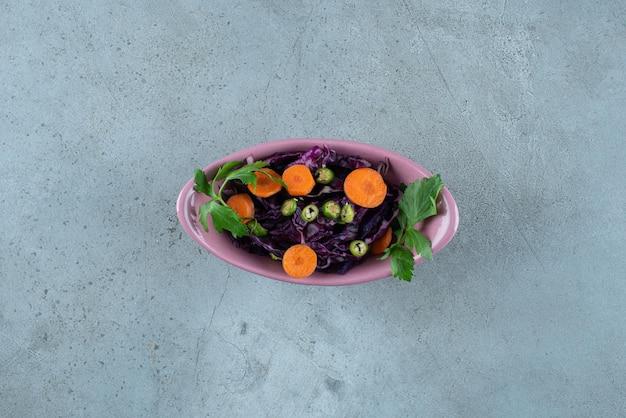 ピンクのボウルにさまざまな野菜と緑のスライス。