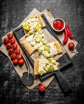 ボウルにチェリートマトとソースを入れた野菜ピザのスライス。黒の素朴な背景に