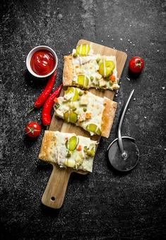 검은 시골 풍 테이블에 그릇에 칠리 페 퍼와 토마토 페이스트와 야채 피자 조각.