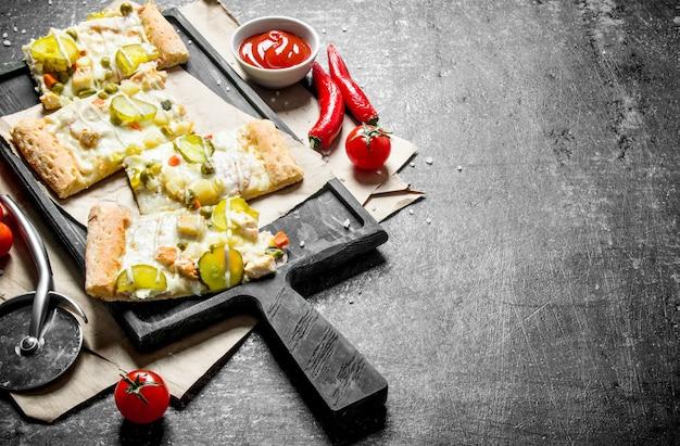 黒の素朴なテーブルの上にきゅうりとチーズソースと野菜のピザのスライス。
