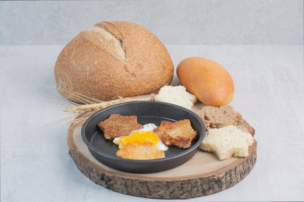 Кусочки белого и черного хлеба с жареным яйцом на деревянной тарелке.