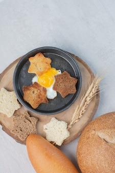 나무 접시에 튀긴 계란 흰색과 갈색 빵 조각.