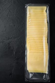 黒いテーブルの上に、密封されたパックの黄色いチーズのスライス