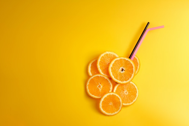 Slices of orange, cocktail tubes, top view, fresh orange juice