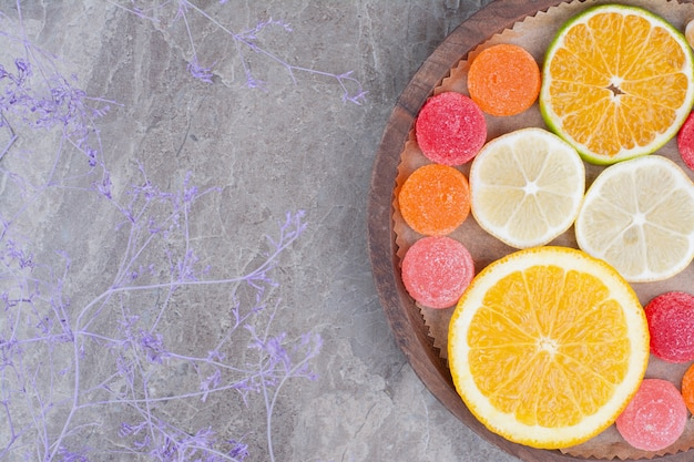 Slices of orange, lemon and candies on wooden plate.