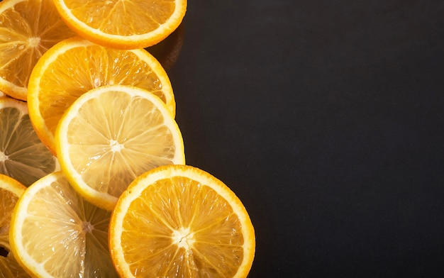 Slices of orange and lemon, isolated on a black.