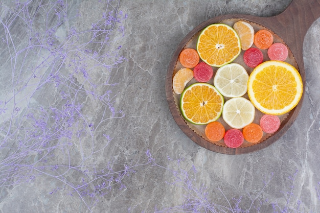 Slices of orange, lemon, tangerine and candies on board.