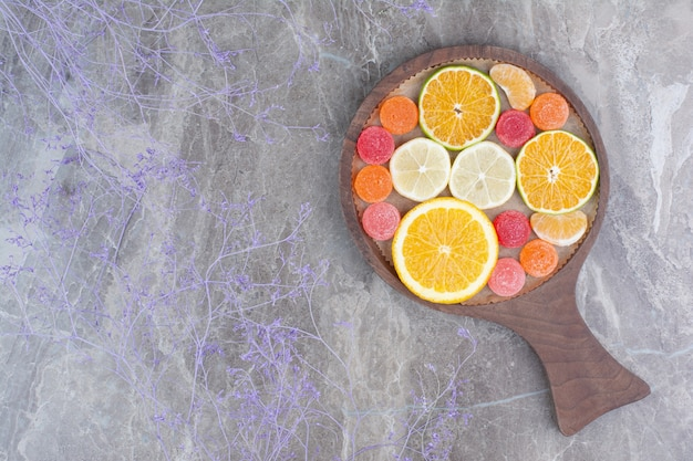 Slices of orange, tangerine and candies on cutting board.
