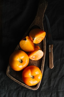 Slices of orange tomatoes on a cutting board and knife