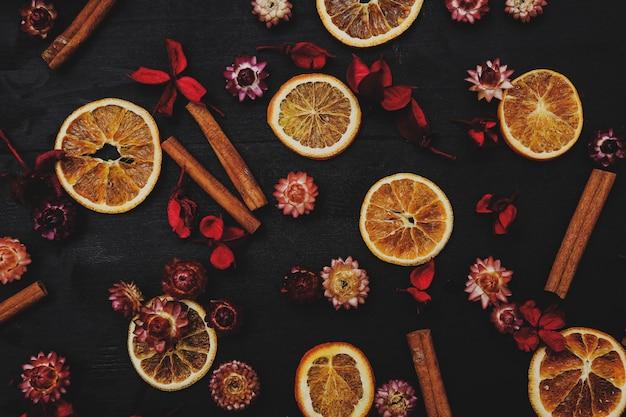 Slices of oranges, cinnamon and flowers