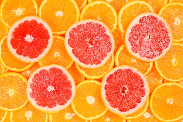 Slices of oranges and a grapefruits as a background.