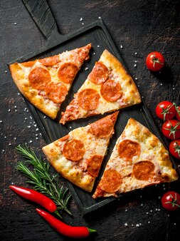 Slices of pepperoni pizza with chili, rosemary and cherry tomatoes.