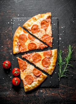 Slices of pepperoni pizza with rosemary and tomatoes on dark rustic table