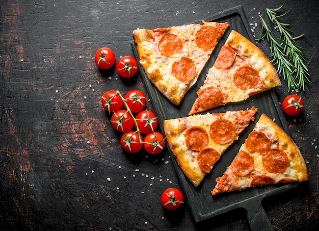 Slices of pepperoni pizza with tomatoes and rosemary. on dark rustic background