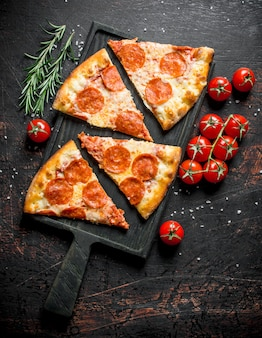 Slices of pepperoni pizza with tomatoes and rosemary.