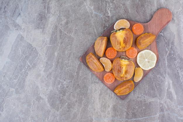 Fette di cachi, limone, mandarino e caramelle a bordo.