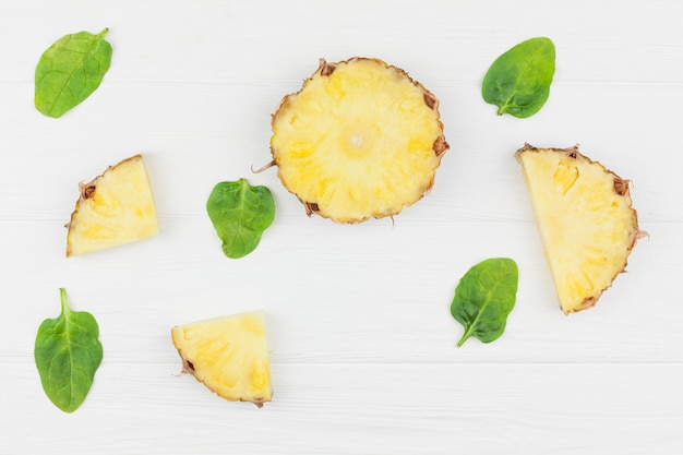 Slices of pineapple among green plant leaves