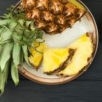 Slices of pineapple with green leaves on plate