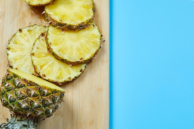 Slices of pineapple on wooden board.