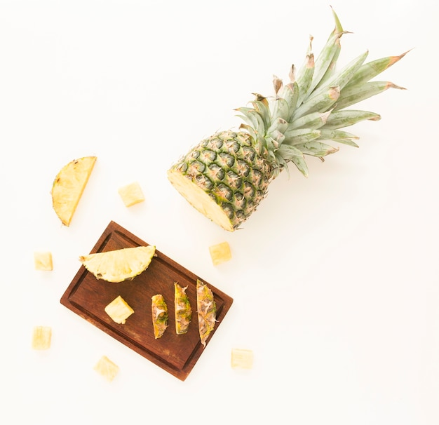 Slices of pineapple on wooden tray isolated on white backdrop